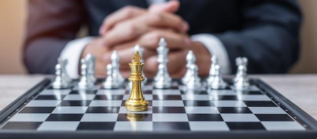 Figura del rey del ajedrez contra el oponente del tablero de ajedrez con el fondo del administrador del empresario.