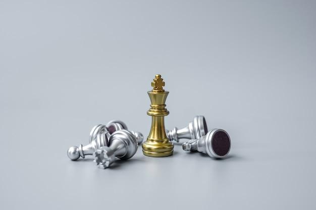 La figura del rey de ajedrez de oro se destaca de la multitud de enemigos u oponentes durante el tablero de ajedrez.