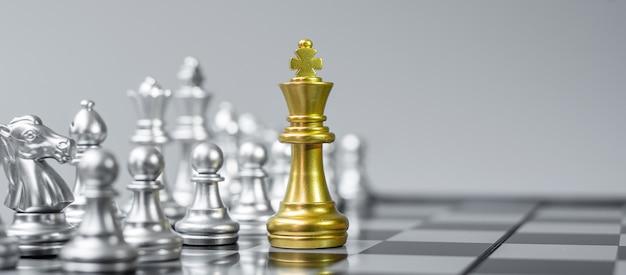 Figura de rey de ajedrez de oro en tablero de ajedrez contra oponente o enemigo.