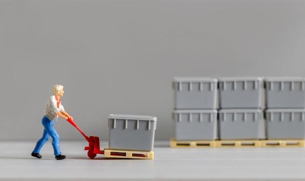 Figura de trabajador de almacén en miniatura usando una mano de remolque de carro para mover cajas