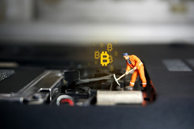 Figura de trabajador técnico de pie en la computadora portátil. concepto de criptomoneda bitcoin.