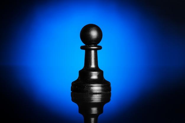 Figuras de ajedrez en negro con luz de fondo azul