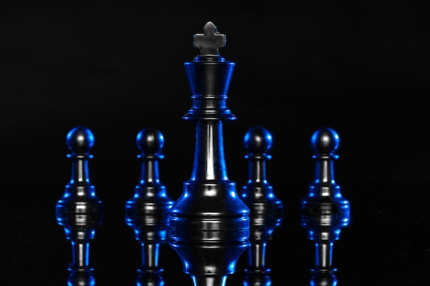 Figuras de ajedrez sobre fondo negro con luz de fondo azul