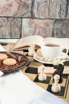 Figuras de ajedrez, una taza de té, un libro y galletas.