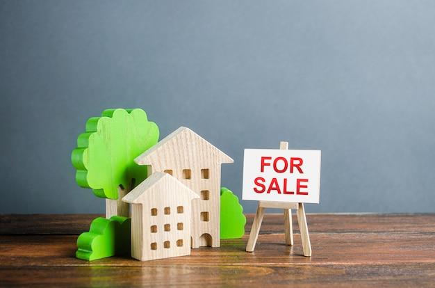 Figuras de casas y un cartel de caballete para la venta. compra y venta de bienes inmuebles