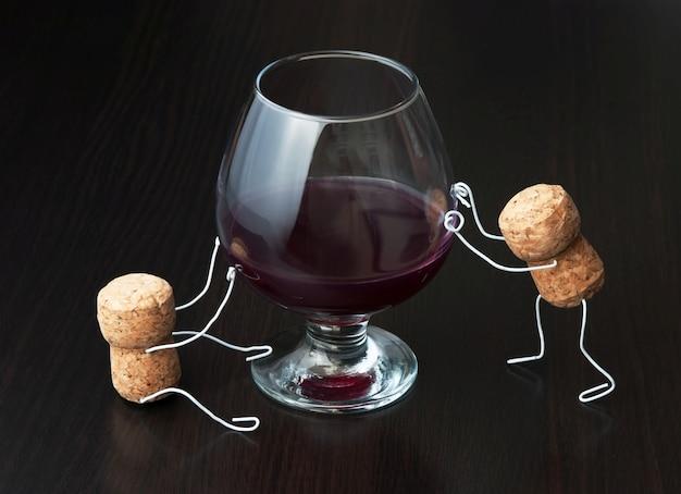 Figuras de corchos de vino y una copa de vino.