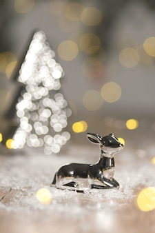 Figuras decorativas de un tema navideño. estatuilla de un ciervo acostado cerca de un árbol de navidad.