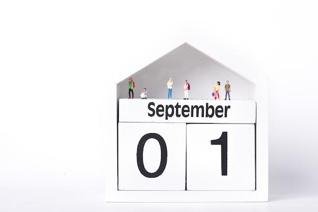 Figuras de estudiantes de pie sobre un calendario que representa el primero de septiembre