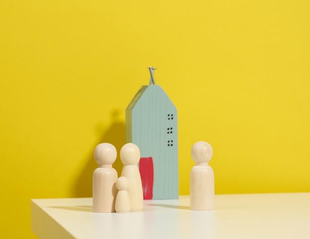 Figuras familiares de madera, casa modelo sobre fondo amarillo. compra de bienes raíces, concepto de alquiler. mudarse a nuevos apartamentos