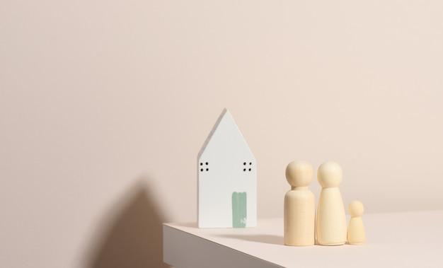 Figuras familiares de madera, casa modelo sobre fondo beige. compra de bienes raíces, concepto de alquiler. mudarse a nuevos apartamentos