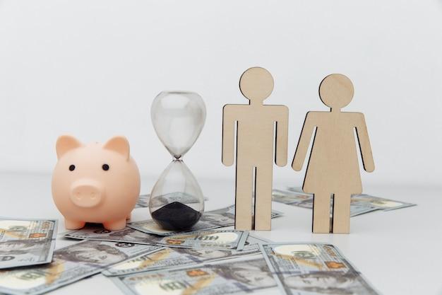 Figuras familiares de madera y hucha rosa en billetes de dólar, concepto de ahorro.