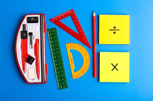 Figuras geométricas de vista frontal con lápiz y pegatinas sobre superficie azul