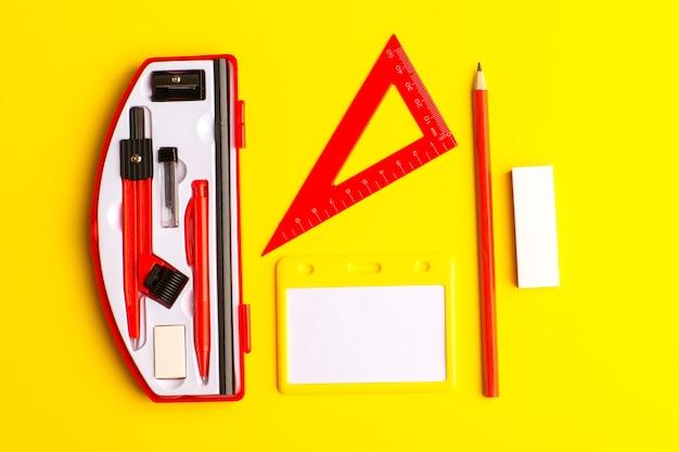 Figuras geométricas de vista frontal con lápiz sobre la superficie amarilla