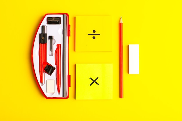 Figuras geométricas de vista frontal con pegatinas y lápiz sobre superficie amarilla