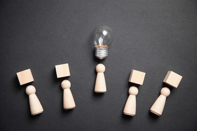 Figuras humanas de madera con cubos y bombilla. idea