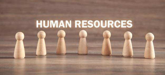 Figuras humanas de madera. hora. recursos humanos
