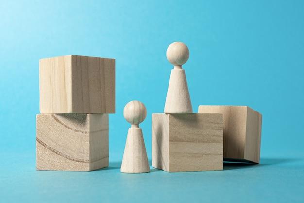 Figuras de madera como personas concepto de construcción y destrucción fondo azul