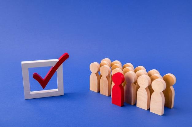 Figuras de madera de empleados de pie detrás de su líder votando
