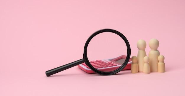 Figuras de madera de la familia de los hombres pequeños, lupa y calculadora sobre una superficie rosa