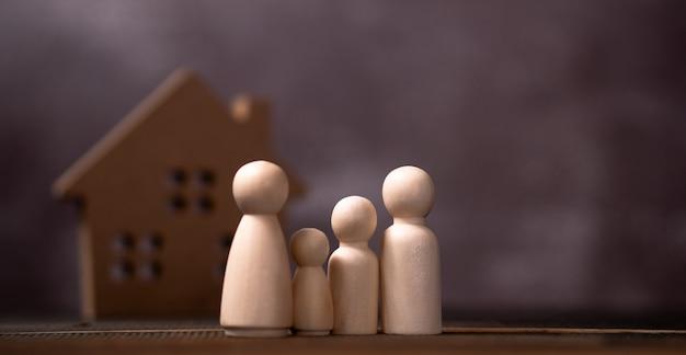 Figuras de madera familia de pie delante de una casa de madera. el concepto de protección y seguridad.