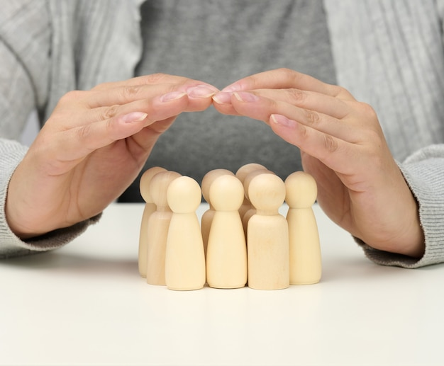 Figuras de madera de hombres, una familia custodiada por dos manos femeninas. ayuda, seguro de vida, seguridad