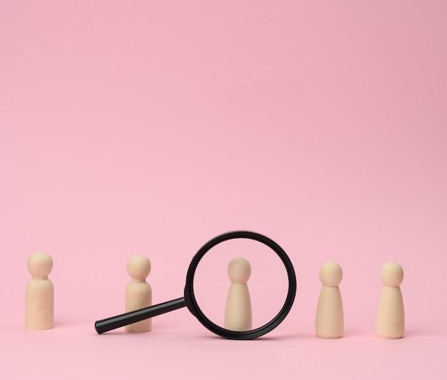 Figuras de madera de hombres parados sobre una superficie rosa y una lupa negra