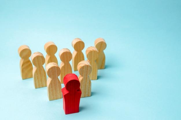 Figuras de madera de personas. el jefe del equipo de negocios indica la dirección.