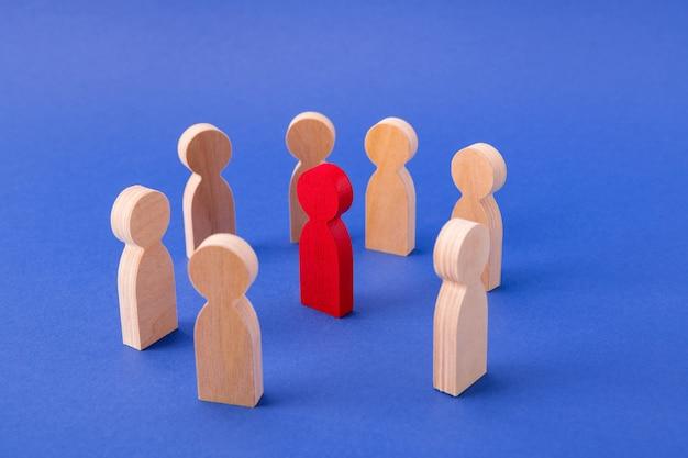 Figuras de madera de personas de pie en círculo intimidando a un chico