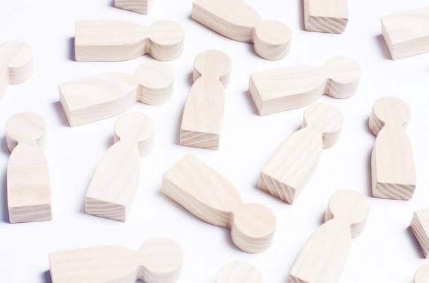 Figuras de madera de personas sobre un fondo blanco.