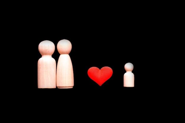 Figuras de madera que representan el amor de la familia, los padres que quieren adoptar un niño.