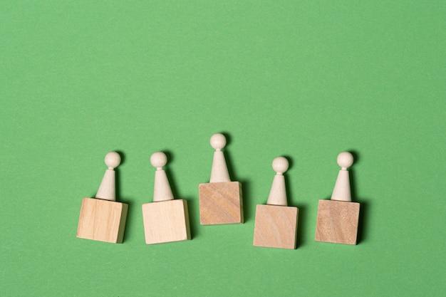Figuras de madera sobre fondo verde con espacio para texto