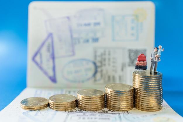 Figuras en miniatura de padre e hijo con maleta y pila de monedas y pasaporte