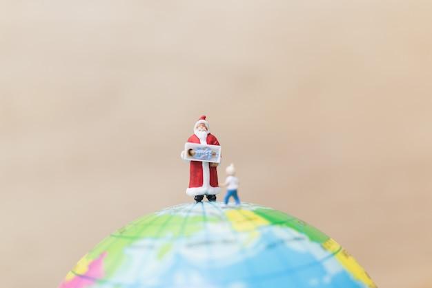 Figuras en miniatura de santa claus con regalo