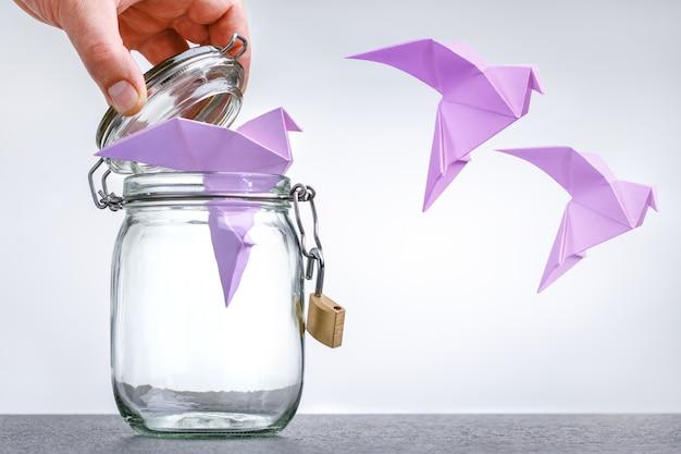 Figuras de palomas de papel volando en su jaula, concepto de paz