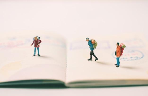 Figuras de personas en miniatura con mochila caminando y de pie en la página del pasaporte con sellos de inmigración, viajes y concepto de vacaciones