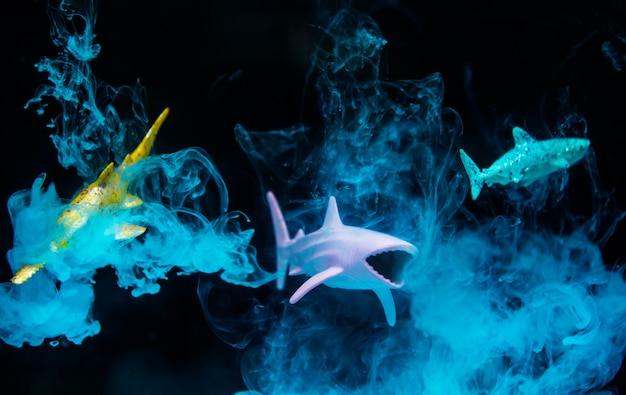 Figuras de tiburón en agua con efecto negativo y humo azul.