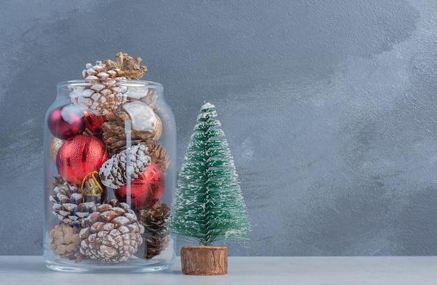 Una figurilla de árbol y un frasco caído lleno de adornos navideños en la superficie de mármol