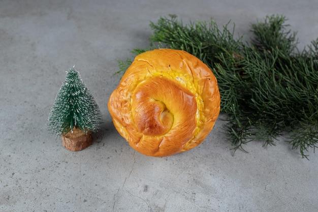 Figurilla de árbol pequeño, panecillo dulce y rama de pino dispuestas sobre mesa de mármol.