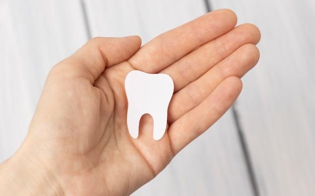 Figurilla de diente en mano sobre fondo de madera. medios para cuidar la cavidad bucal.