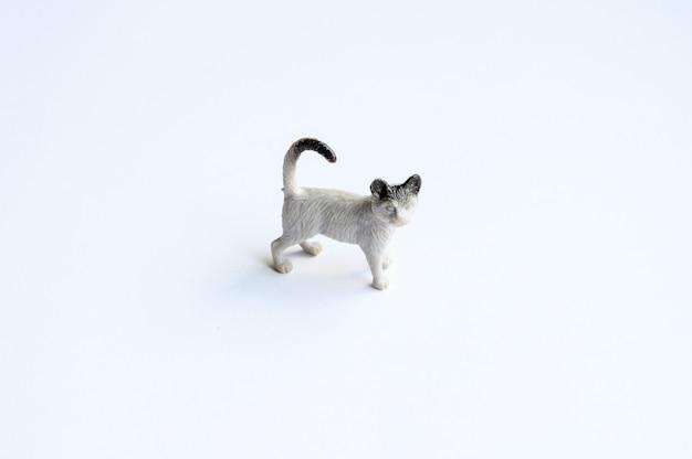 Figurilla de un gato sobre fondo blanco.