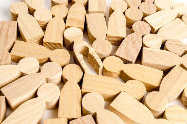 Figurilla de madera de un hombre con una forma de niño vacía dentro del cuerpo entre otras personas.