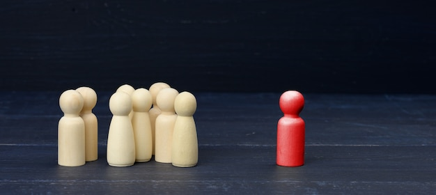 Figurilla roja de un hombre entre la multitud sobre una superficie azul. el concepto de búsqueda de empleados, personas con talento. un administrador eficaz. no como todos los demás, persona tóxica rodeada
