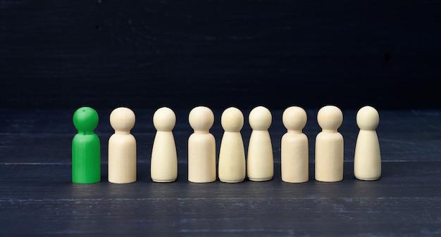 Figurilla verde de un hombre entre la multitud sobre una superficie azul. el concepto de búsqueda de empleados, personas con talento. un administrador eficaz. no como todos los demás