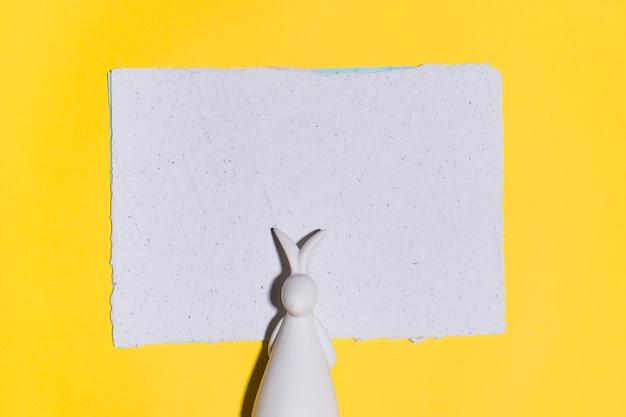 Figurita de conejo con papel sobre mesa amarillo.