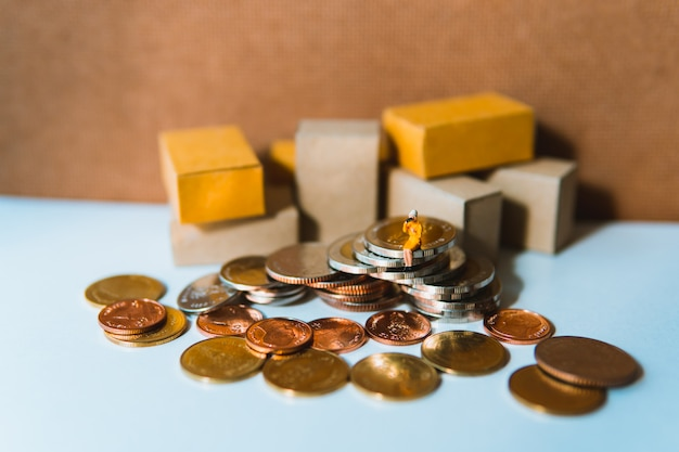 Figurita mujer sentada en la pila de monedas con cajas de cartón