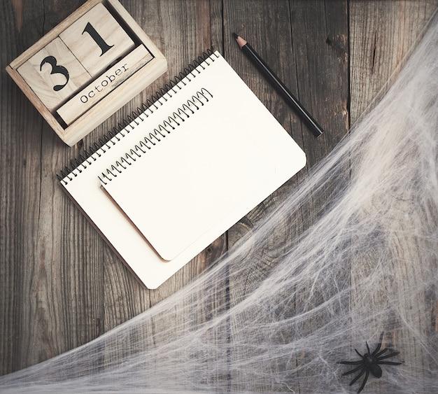 Figuritas de araña negra y reloj retro de madera hecho de bloques con fecha del 31 de octubre