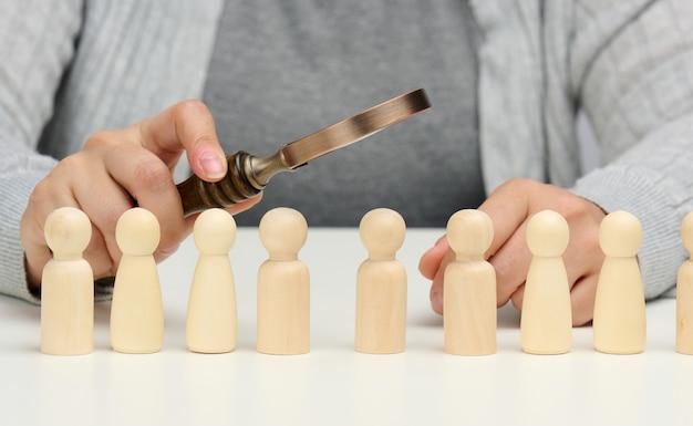 Figuritas de hombres sobre una mesa blanca, una mano femenina sostiene una lupa sobre uno. concepto de búsqueda de empleados en la empresa, reclutamiento de personal, identificación de personalidades fuertes y talentosas