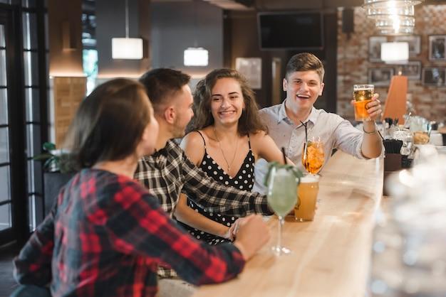 Fila de amigos disfrutando de bebidas en el pub