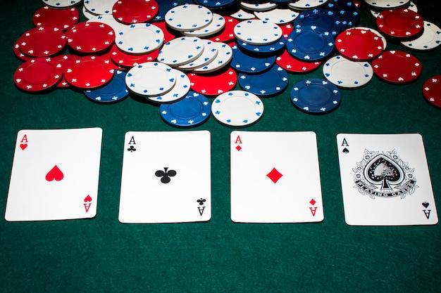 Fila de ases y fichas de casino en la mesa de póquer verde