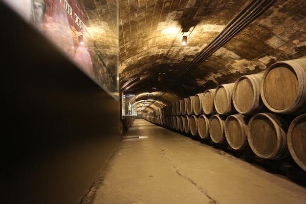 Fila de barricas viejas para el envejecimiento del vino en la bodega.